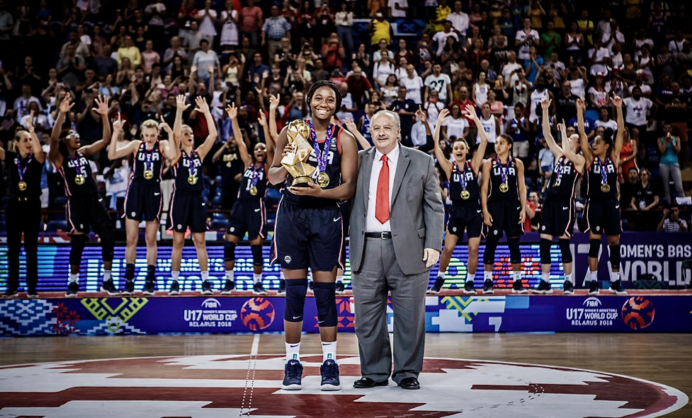 Aliyah Boston poses with the trophy after Team USA won the gold medal run at the 2018 U17 Women's World Cup in Belarus. In the background, her teammates celebrate with their gold medals. (Photo by FIBA)