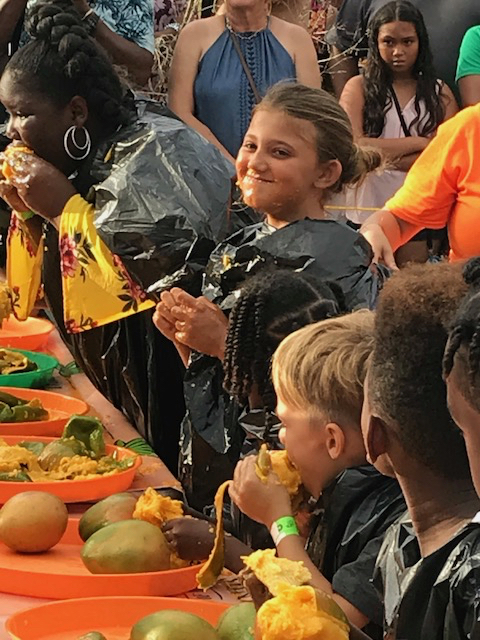 Peyton Schindler grins Sunday after finishing her fourth mango to win the children's division of the Mango Eating Contest at Mango Melee.