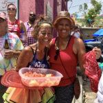 Jodi Tanino and Wanda Burgos enjoy some cooling fresh fruit during the 2019 parade. (Amy Roberts photo)