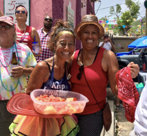 Jodi Tanino and Wanda Burgos enjoy some cooling fresh fruit during the 2018 parade. (Amy Roberts photo)