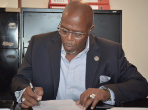 Senate President Myron Jackson signs documents finalizing the purchase of the new St. Croix legislative building.