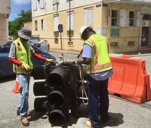 Two Department of Public Works employees prepare a new traffic light to hang over an intersection.