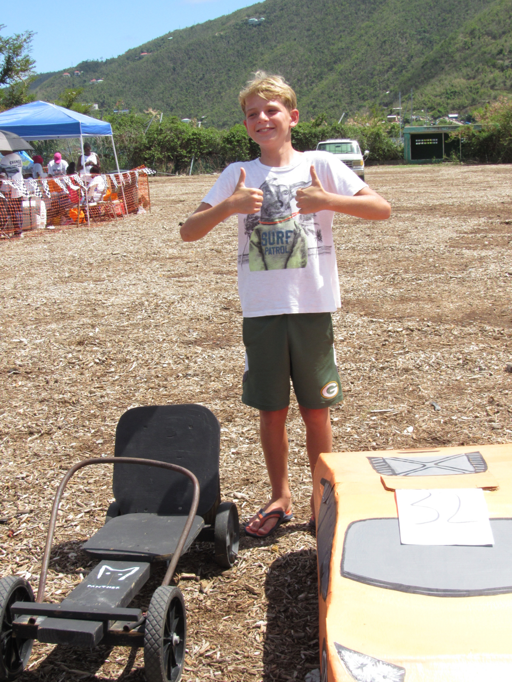 Henry Radcliffe, 11, shows off the go cart and cardboard 'Lamborghini' he built.