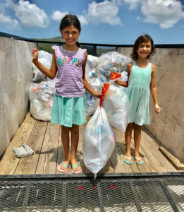 Sisters Isabel and Sofia Melendrez joined the crew Saturday as they bring in recyclable plastic.