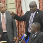 Sen. Marvin Blyden, seated, and Neville James, center, speak to Senator-at-large Brian Smith, who was absent during the zoning votes that allowed construction of a gas station on property he owns on St. John. (Photo by Barry Leerman for the V.I. Legislature)