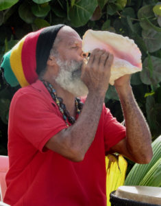 St. John culture bearer Delroy Anthony blows the conch shell as visitors arrive for the start of the 34th Fortsberg History Tour.