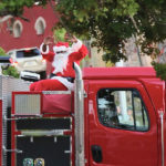 Santa arrives for the Miracle on Main Street riding a red-nosed fire truck.