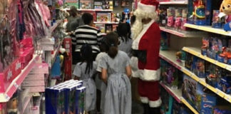 Santa Claus escorts students through the toy section.