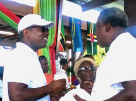 Gov. Albert Bryan chats with We Grow Food, Inc. President Eldritch Thomas on Sunday at the 22nd Rastafari Cultural and Agricultural Fair.