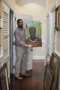 Julio Encarnacion holding painting 'Strength and Power,' artist unknown, during assessment and inventory of St. Thomas Government House Annex. (Photo submitted by Julio Encarnacion)