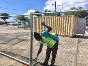 Demar Lewis installs fencing around the Customs lot in Cruz Bay.