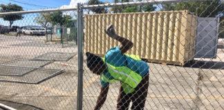 Demar Lewis installs fencing around the Customs lot in Cruz Bay.