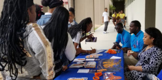 Student look at materials from Lincoln University at Tuesday's college fair. (Photo provided by Cenita Heywood)