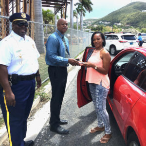 From left, STT Traffic Commander Lt. Lionel Bess and acting V.I. Police Commissioner Jason Marsh reward an anonymous female motorist. (VIPD photo)