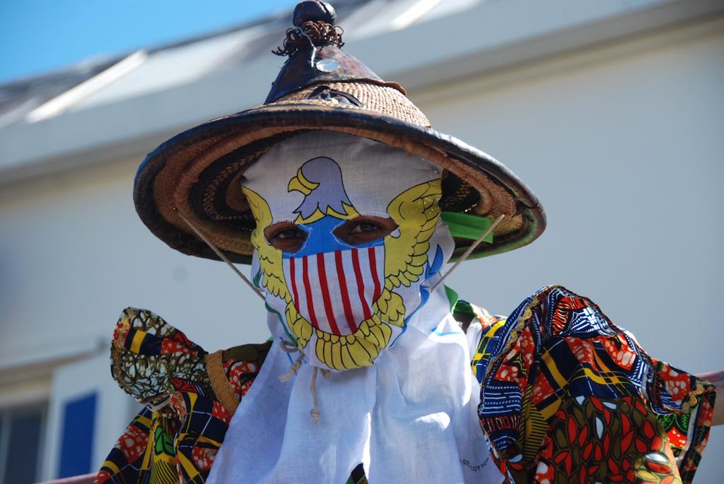 A mocko jumbie wears a mask showing the USVI symbol. (Photo by Willard John)