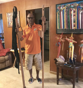 Willard John displays a pair of handmade stilts. (Elisa McKay photo)