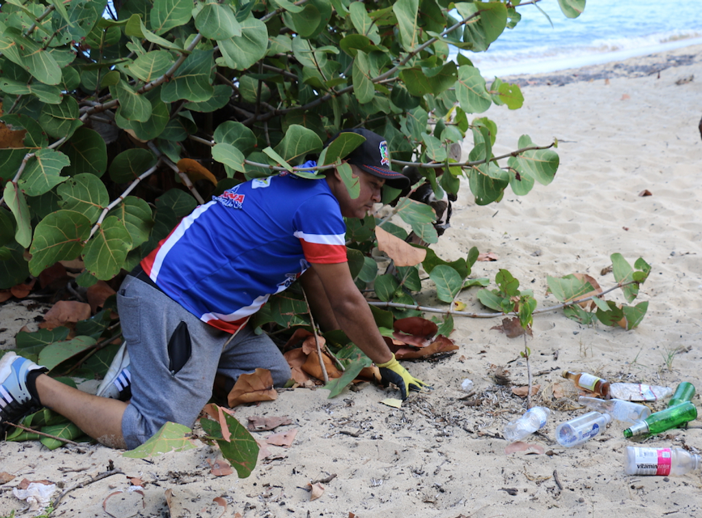 Wilfrido Ferreras, vice president of Dominicans in Action Committee, dig trash out from under a seagrape tree. Plastic bottles, beer bottle and foam food plates/containers were the predominant items found and removed in approximately 45 large bags of trash. (Linda Morland photo)