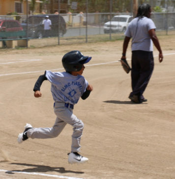 Rashaun Petersen tries to beat the throw to first base as the 7 to 9 year olds open the new season.
