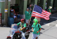 Tony Emmanuel carries the flag early in the parade, the Stars and Stripes snapping in the wind as he rides. (Linda Morland photo)