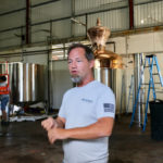 Todd Manley, co-founder of Sion Farms Distillery, stands amid the hustle and bustle of the equipment being installed in the facility. (Linda Morland photo)