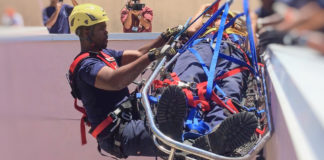 """Firefighter Bruce Rhymer supports a """"patient"""" while rappelling down the side of Schneider Hospital during a rope rescue exercise."""
