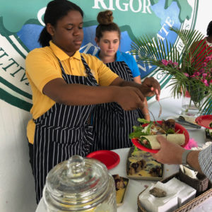 Raynesha Noel and Lily Porter serve JAVI guests at Gift Hill School. (Amy Roberts photo)