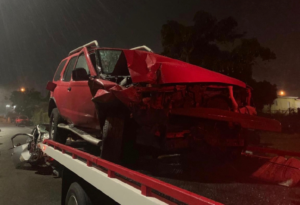 A mangled red Nissan sedan is loaded onto a tow truck. It was struck by the damaged silver Toyota Yaris seen in the background. (VIPD photo)
