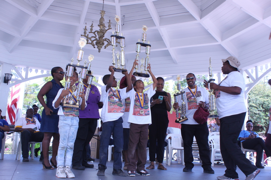 Students from the Seventh Day Adventist School raise their large trophies after winning the Dem Coal Pot youth culinary event with a score of 375 points. (Bethaney Lee photo)