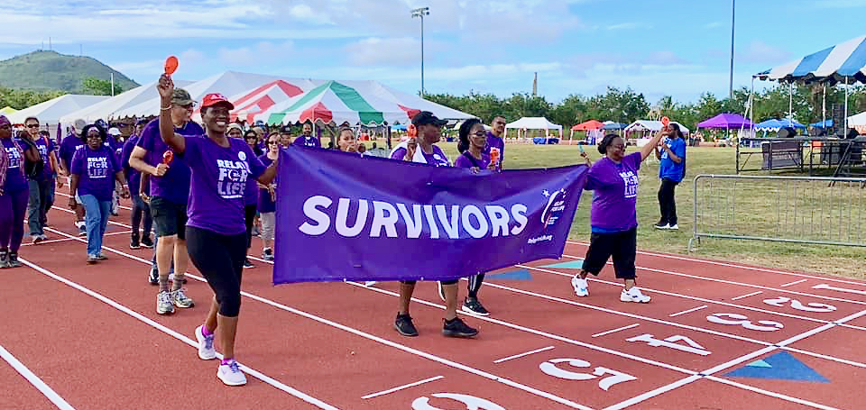 Cancer survivors march joyously around the track during Relay for Life. (Photo by Dona Jones)