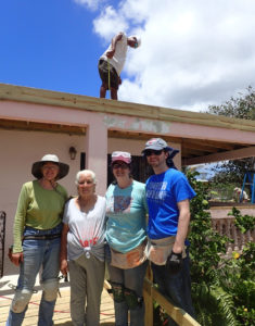 Terry Cline, Grimilda Quinones, Darion Barnhart and Danny Barnhart take a break from working on Quinones roof.