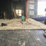 Workmen apply new plywood flooring on top of the old wooden floor. (Eliza McKay photo)