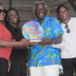 """St. Croix Rising Stars Youth Steel Orchestra director Natasha Williams-Modeste presents an appreciation award to St. John Festival Committee members Alecia Wells, Liston """"Matey"""" Sewer, and Leona Smith"""