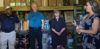 Ian Samuel, left, and Bill and Hillary Clinton, listen to Meaghan Enright explain construction issues on St. John. (Amy Roberts photo)