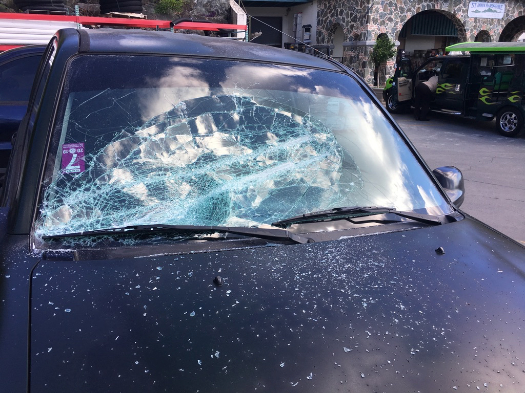 Motorists document damage to their vehicles in the St. John Marketplace parking lot on Wednesday. (Judi Shimel photo)