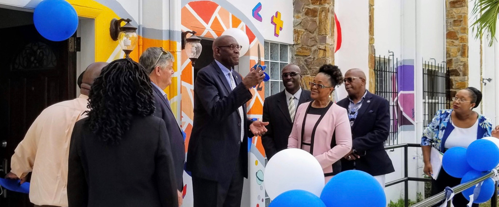 UVI President David Hall raises a pair of scissors during the ceremonial ribbon cutting that marks the opening of the universities first childcare facility and diagnostic center. (Source photo by Bethaney Lee)