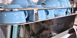 A rack full of blue mugs sits ready to be used by employees who create handcrafted brews for customers.