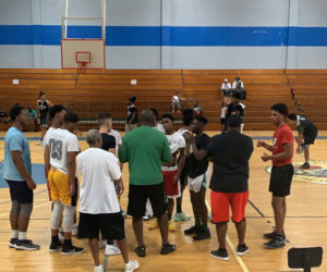 Coach Jareem Dowling, back to the camera in the green shirt, talks to the team at practice. (Submitted photo)