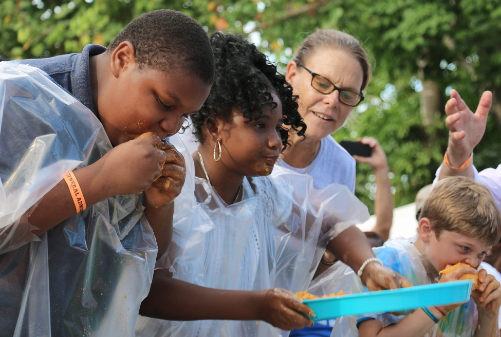 The winner of the children's mango eating contest was Reyonce Roach, center. (Source photo by Linda Morland)