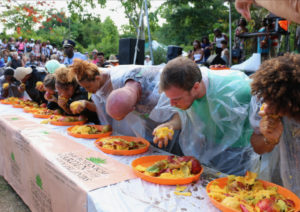 Single-handed mango eating was the rule for the adults and they attempted to get through the large plate of mangos. (Source photo by Linda Morland)