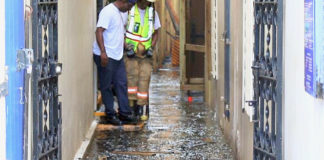 Firefighters navigate the flooded passageways of Royal Dane Mall early Friday morning after the fire. (Source photo by James Gardner)