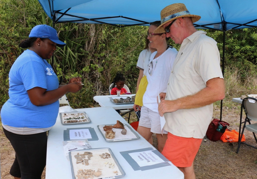 Alicia Olewale, assistant professor of anthropology at the University of Tulsa, interprets one of the artifacts on display at Little Princess to Jeffrey Miller and Jennifer Miller. (Source photo by Linda Morland)