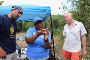 Alicia Odewale studies a new piece of tile that was found on the grounds as William White, left, and Jeffery Miller look on. (Source photo by Linda Morland)