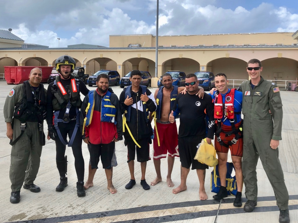 The aircrew of an MH-65 Dolphin helicopter from Coast Guard Air Station Borinquen and a Royal Netherlands Navy helicopter rescue swimmer take a photo with the four survivors of a capsized vessel, after they were rescued earlier 45 miles south of Vieques, Puerto Rico July 14, 2019. The rescued boaters were transported to St. Croix, where they were received by Customs and Border Protection authorities. (U.S. Coast Guard photo)
