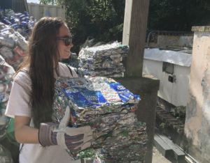 Volunteer Maven Parsil stacks crushed aluminum cans at Island Green Living Association. (Source photo by Amy Roberts)