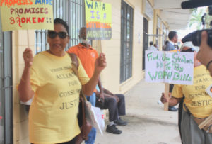 Activists wave signs protesting the proposed WAPA rate increase outside Wednesday's meeting. (Source photo by Bethaney Lee)