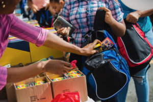 Volunteers stuff supplies into new backpacks Tuesday. (Photo by Samuel Hodges for Home Depot)