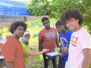 Kitty Edwards of DPNR assists CAHS students Khaleel Smith, Elijah Rabatt Rae'Heim White, and Reuben Martin with trash collection weigh-in at Brewers Bay. (Source photo by Teddi Davis)