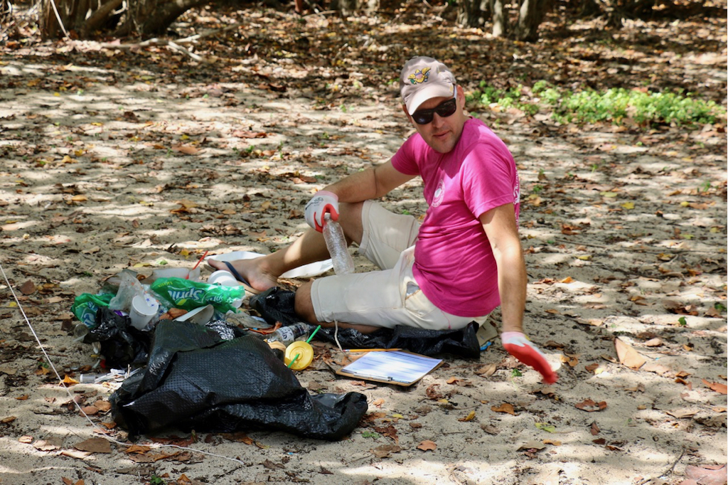 Sorting a bag of trash, Chris Sublett carefully counts and records each object at Southgate beach. )Source Photo by Linda Morland)