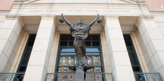 """A statue of """"Blind Justice"""" graces the entrance to the Albert V Bryan U.S. Courthouse in Alexandria, Virginia, where Scott MacKenzie pled guilty to election law violations. (Shutterstock image)"""