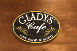 A vintage sign, salvaged from the embers of the devastating blaze the razed the old restaurant, adorns the wall at Gladys' Cafe. (Source photos by Teddi Davis)
